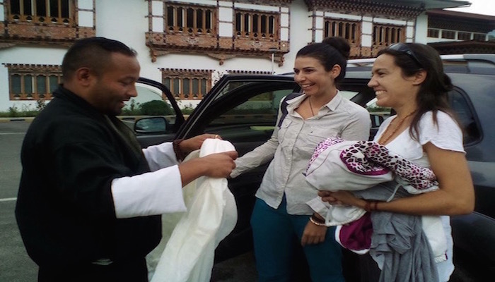 Guide welcoming guest with white khadhar at Paro International airport
